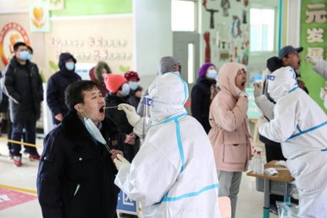 People are seen undergoing coronavirus swab tests at a testing center set up at a primary school in Shenyang. Shenyang is testing millions of residents following a small but persistent growth in COVID cases.